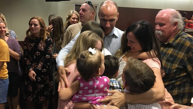 Janna and Brian Bentley embrace their seven children following the jury's not-guilty verdict on Aug. 9, 2017, in Mesa. The Bentleys were charged with child neglect and contributing to the delinquency of a child after their young son hid outside overnight.