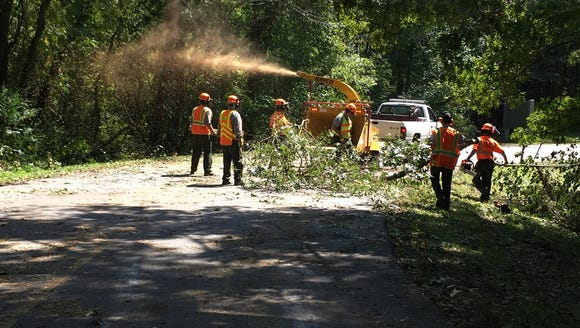 Crews work to clean up debris blown into the road on