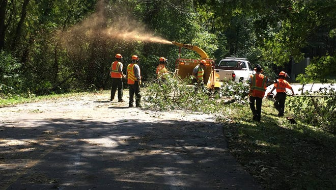 Crews work to clean up debris blown into the road on the Blue Ridge Parkway near Asheville.