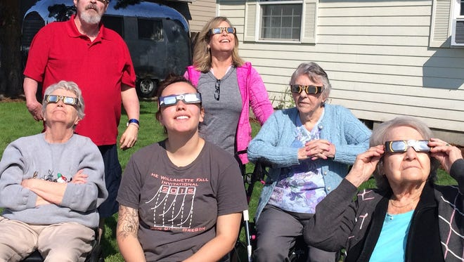 Folks take in the eclipse at the Open Arms Adult Care foster home.