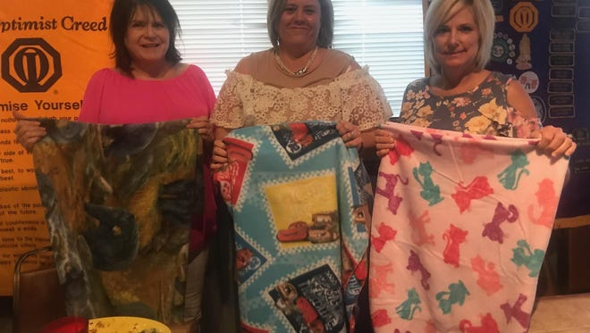 Red River Optimist Club President-Elect Johnna Bounds, left, Keri Goins, Child Care Inc., gather handmade blankets donated to the children at Farris Early Head Start. Lisa Little, right, is with Head Start.