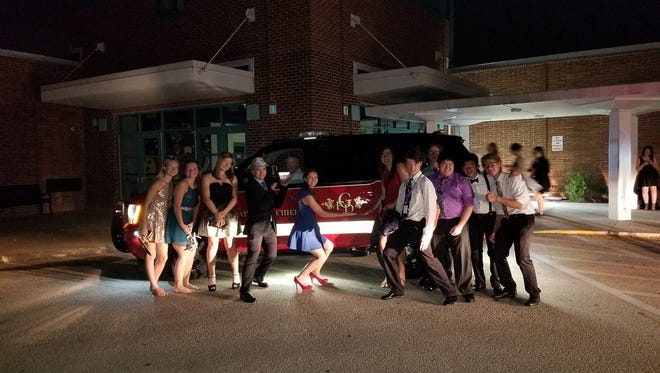 Whitnall High School students pose for a photo with a Greenfield Fire Department vehicle at the Homecoming dance after the department showed up to re-supply the event with power.