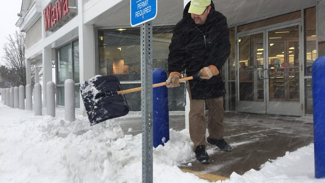 John Venters, assistant manager for the northside Salisbury Wawa, shovels snow outside the store on Jan. 4, 2018.