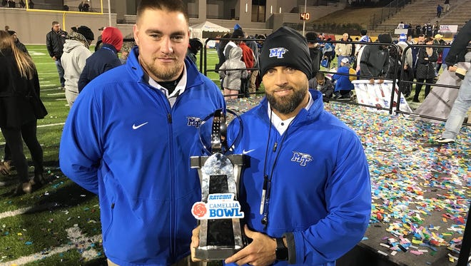 MTSU football strength coach Jason Spray hoists the Camellia Bowl trophy alongside his assistant, Lance Campbell, after the Blue Raiders defeated Arkansas State, 35-30, in Montgomery, Ala., on Dec. 16, 2017.