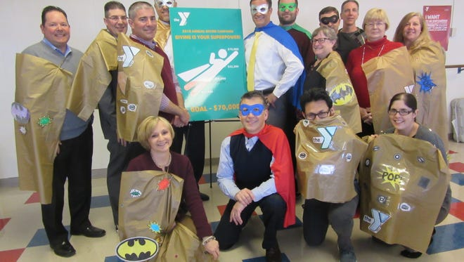 """Some Cumberland Cape Atlantic YMCA Board members and staff donned super hero capes, made by children in the before and after school programs at the YMCA, to celebrate the announcement of the theme for the annual campaign, """"Giving Is Your Superpower."""""""