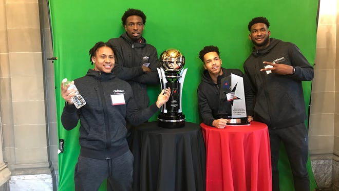 University of Cincinnati basketball players (L-R) Justin Jenifer, Nysier Brooks, Cane Broome and Eliel Nsoseme pose with some of their AAC hardware before Monday's team banquet.