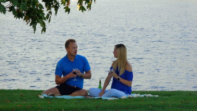 Krista Hempel and Grant Hempel enjoy some wine by Lake Lakengren while discussing their final decision as seen on HGTV's Lakefront Bargain Hunt.