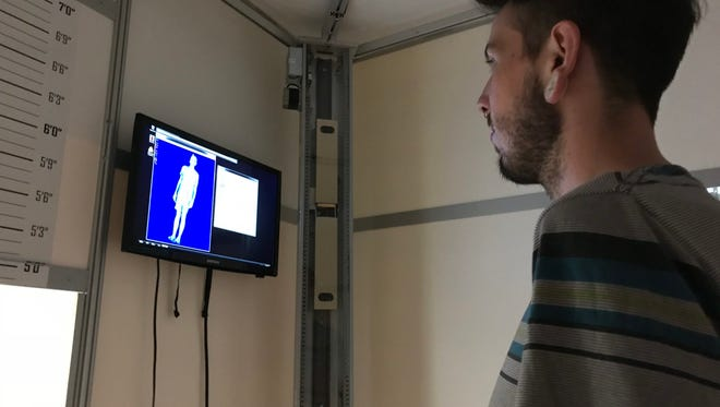 Graduate student Tyler Klene looks at the image of his body from inside the scanner.