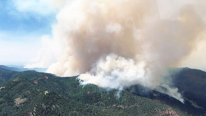 This aerial photo, taken Monday above the 171 road, looks northeast and shows the main fire moving south, part of the fire in Buck Creek drainage and, where the smoke is thinner, the planned burnout area.