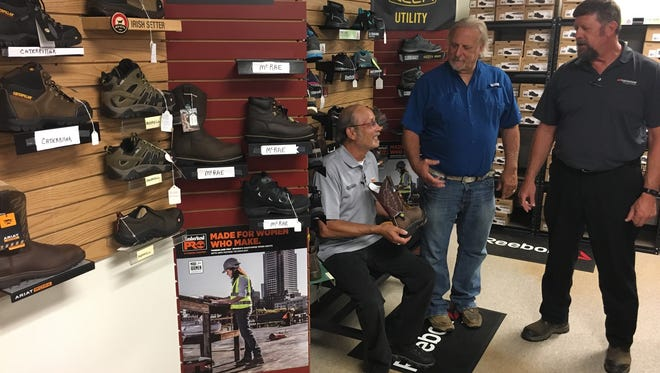 Jimmey Sodanski, seated, manages the new Boots Plus store inside Clarksville's Hankook Tire plant. He's shown with Boots Plus owner Russ Hayes, center, and David E. Smith of Hankook's safety team.