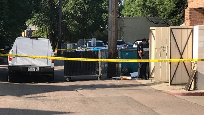 Fort Collins police investigate the discovery of a man's body in an alley off of South College Avenue on Friday morning.