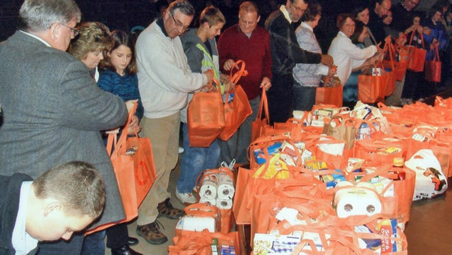 Spencer area residents form a human chain as they pass the grocery-filled bags to an awaiting trailer outside the LuCille Tack Center for the Arts during the 2011 Spencer Community Thanksgiving Service.