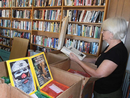 Book Depot volunteer Wilma Johnson sorts through a century of National Geographic magazines.