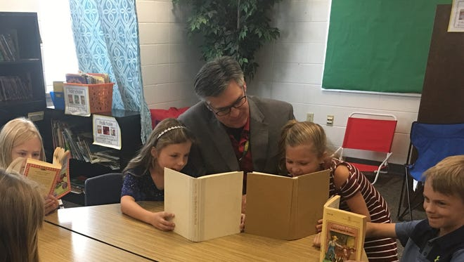Mountain Bay Elementary students in Weston read with Principal Patrick Phalen. Mountain Bay has been named to the National Blue Ribbon Schools program.