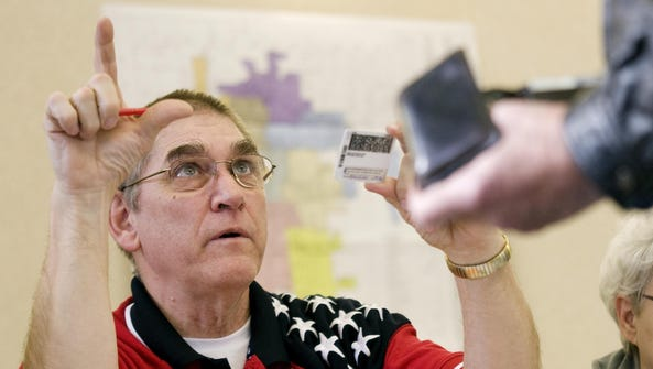 John Kleinmaus of West Bend helps instruct a voter