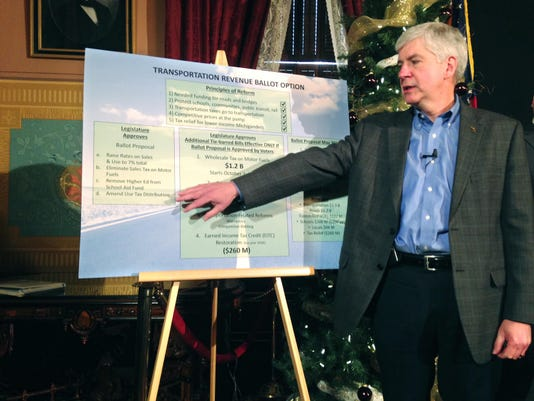 Snyder signs road-spending bills with tax hikes
