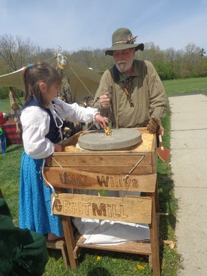 Grassy Run Historical Arts Committee member and New Richmond resident Bob Taylor watches young camper Ella Luke of Fayetteville grind corn the old fashion way at this year's Grassy Run (living history) Rendezvous in Williamsburg April 24-26. Ella was camping with her mom, Rhonda, and her siblings, Emma and Robbie, all Grassy Run members.