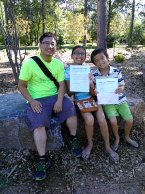 Leo Moua, 26, sits in the Monk Botanical Gardens with his niece and nephew, Sarina and Kenji Thao (left to right). The children are showing their completed scavenger hunt sheets.