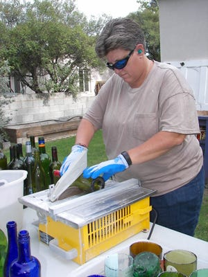 Green Chamber of Commerce Executive Director Carrie Hamblen prepares a wine bottle for a do-it-yourself patio in her backyard.