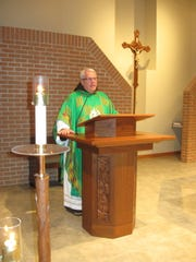 Fr. Gary Wegner stands at a podium, ready to speak