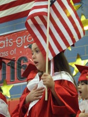 Alea Rose Mendes leads the Pledge of Allegiance during the Pre-Kindergarten graduation at St. Stanislaus Kostka School in Sayreville. Kindergarten and eighth-grade commencement ceremonies also were conducted at the Roman Catholic school.