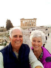 Jay and Linnea Young take a selfie on the Acropolis in Athens, Greece, with the Parthenon, the temple dedicated to Athena, in the background.