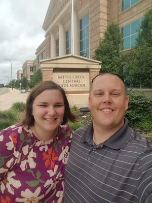 Chris Momcilovich poses with his wife, Kari, in front of Battle Creek Central High School.