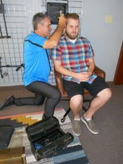 J.R. Martin examines Carson Stilson's ears. Stilson is the Digital Content Producer at Squatty Potty.