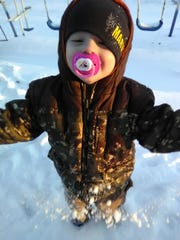 Aaron Girten smiles for the camera while playing in the snow.