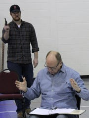 """Steve Faehnle, director of """"They Might Be Giants,"""" reads for two absent actors during rehearsal, unaware in this scene of the approach of a man with a gun (Jacob Snowden)."""