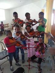 A beginner string class in Cange, Haiti.