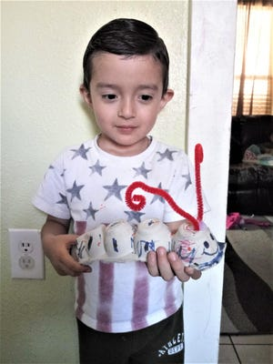 Young Isaac Rodriguez with an art project completed at home through the arts center's remote outreach.