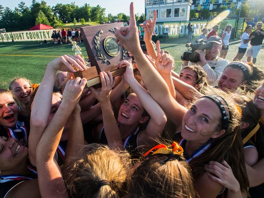 Center, Middlebury's Andi Boe holds up the 2018 Vermont Div. 1 high school girl's lacrosse State Championship trophy with her teammates after defeating CVU.