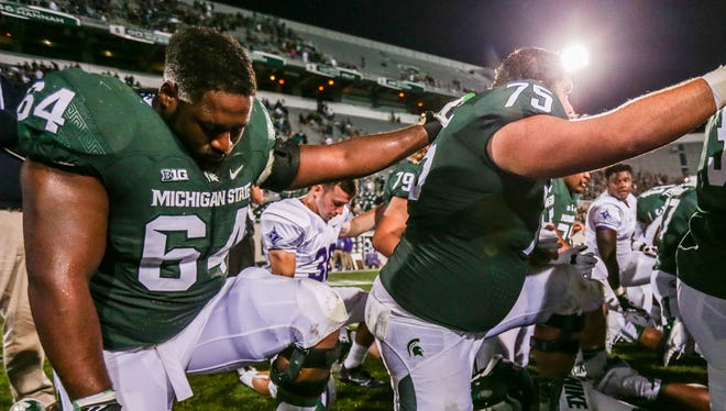 Michigan State Spartans' Brandon Clemons prays after a win against Furman at Spartan Stadium in East Lansing on Friday, Sept. 2, 2016.