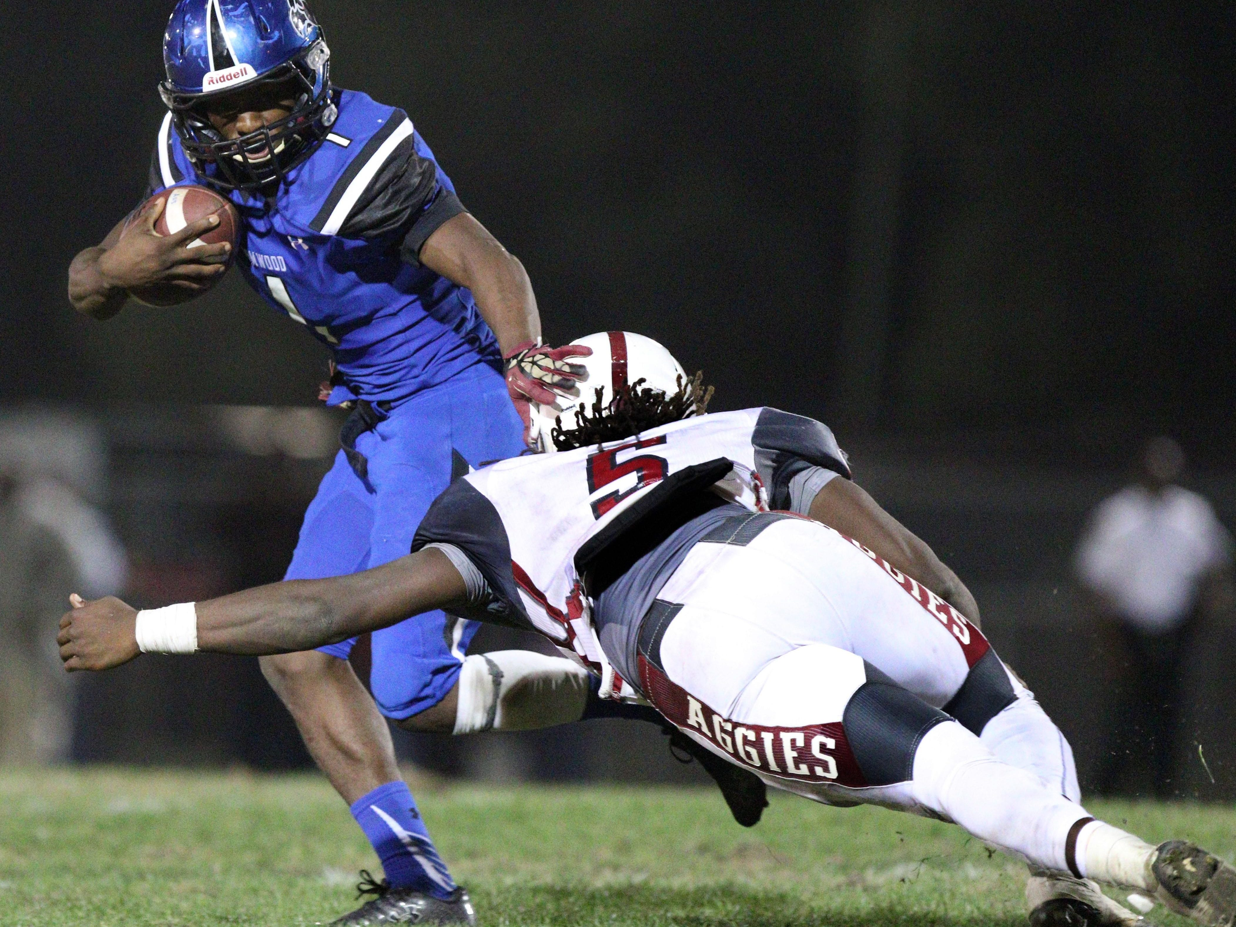 SEFFNER, FL. 12/4/2015 -- Armwood Hawks quarterback Darrian McNeal tries to escape the diving tackle of Tate defensive end Alonte Thompson during Friday's Class 6A state semifinals game at Lyle Flagg Field. The Hawks went on to defeat the Aggies 53-19 to advance to the stat title game Saturday in Orlando. Photo by BILL WARD/PNJ
