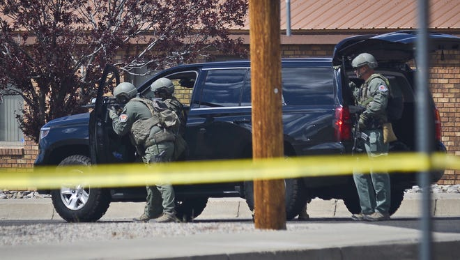Police respond to the scene of a double homicide at a Vietnamese restaurant near San Mateo and Montgomery, in Albuquerque, N.M., Friday, April 1, 2016.