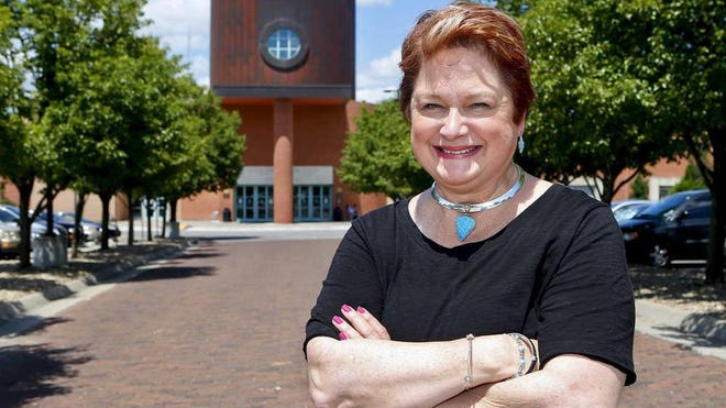 Gina Millsap stands in front of Topeka and Shawnee County Public Library in 2016. Millsap will retire as CEO of the library in December.