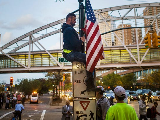 A man places a U.S. flag in memory of the victims of Tuesday's truck attack on the bike path near the crime scene on Thursday.