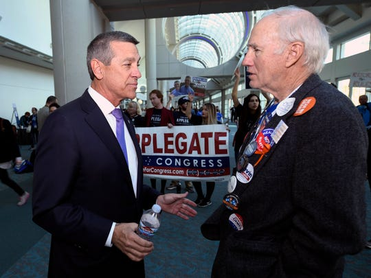 Democratic congressional candidate Doug Applegate, left, talks with delegate Stephan Bartram in front of supporters at the 2018 California Democrats State Convention Saturday, Feb. 24, 2018, in San Diego. (AP Photo/Denis Poroy)