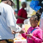 Alicia Gayle, 8, of Rochester sells a cup of lemonade to Cleveland Blocker Jr. of Rochester, during Lemonade Day in 2015. Lemonade Day is a program of Rochester Institute of Technology's Center for Urban Entrepreneurship.