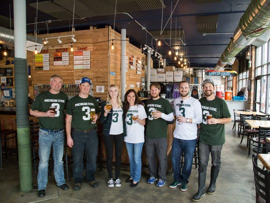"""Katie and Karen Sadler (middle) join the Jagged Mountain Brewery crew in enjoying a taste of """"Hey Diddle Diddle"""" beer to honor Mike Sadler."""