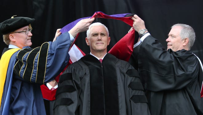Vice President Michael Pence receives a sash representing an honorary degree at the commencement ceremony at Grove City College, Saturday, May 20, 2017, in Grove City, Pa. College Provost Robert Graham, left, and David Rathburn, chairman of the board of trustees of Grove City College, place the sash. (AP Photo/Keith Srakocic) ORG XMIT: PAKS108