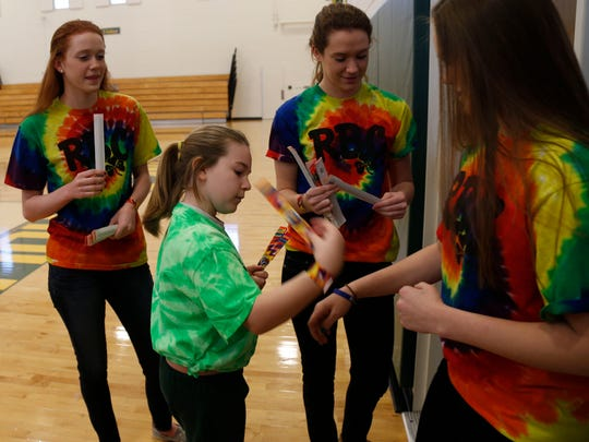 Left to right: Corey Belfort, Kasey Kennedy and Morgan Belfort hand out tie-dye slap bracelets to students at Red Bank Catholic High School.