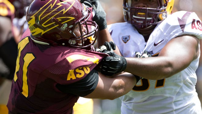 ASU linebacker Viliami Latu is blocked by offensive lineman Evan Goodman during a gold vs. maroon game at Sun Devil Stadium during Fanfest on April 19, 2014.