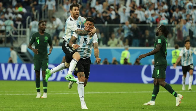 Marcos Rojo of Argentina celebrates with teammate Lionel Messi after scoring his team's second goal to beat Nigeria 2-1 and advance to the round of 16.
