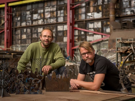 Detroit metal sculptors and brothers Israel Nordin, left, and Erik Nordin pose in their artist workshop called the Detroit Design Center on Sept. 22, 2014. The brothers have created numerous works of public art in and around Detroit.