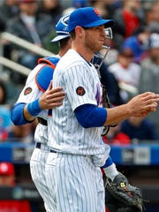 New York Mets catcher Kevin Plawecki, left, consoles Mets starting pitcher Steven Matz after Matz allowed a solo home run to Yadier Molina during the fourth inning of a baseball game against the St. Louis Cardinals, Sunday, April 1, 2018, in New York. (AP Photo/Kathy Willens)