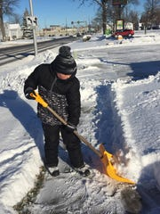Bryce Gee shovels the walks at the Lake Huron Veterinary Clinic in Port Huron.