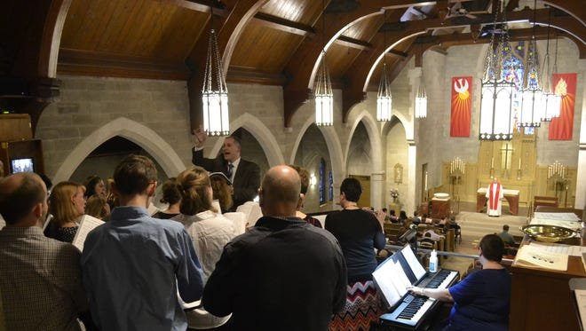 The Rev. Jon Zabell, standing in back, directs the church choir in the refurbished balcony during a dedication service Sunday for the remodeled St. Paul Lutheran Church in Green Bay. Zabell is one of two pastors at the church.
