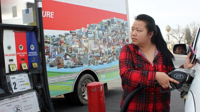Xia Vang of Visalia fills up her family's truck at 4 Season Handy Market on Murray Avenue.